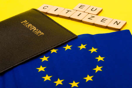 European union concept showing the flag of the EU and a passport on a yellow background with a sign reading EU Citizen