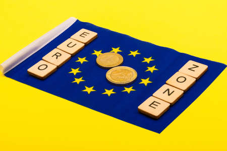 European union concept showing the flag of the EU on a yellow background with a sign reading Euro Zone with a one and two euro coin