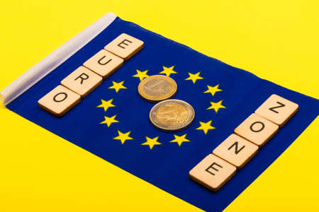 European union concept showing the flag of the EU on a yellow background with a sign reading Euro Zone with a one and two euro coin Reklamní fotografie - 134424312