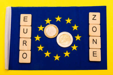 European union concept showing the flag of the EU on a yellow background with a sign reading Euro Zone with a one and two euro coin Reklamní fotografie - 134424314