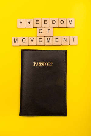 European union concept showing a passport on a yellow background with a sign reading Freedom of Movement Reklamní fotografie - 134424315