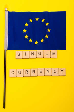 European union concept showing the flag of the EU on a yellow background with a sign reading single currency