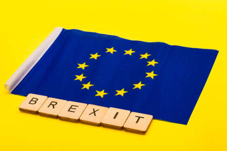 European union concept showing the flag of the EU on a yellow background with a sign reading Brexit