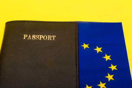 European union concept showing the flag of the EU on a yellow background with a passport 写真素材