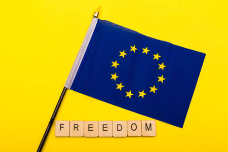 European union concept showing the flag of the EU on a yellow background with a sign reading Freedom