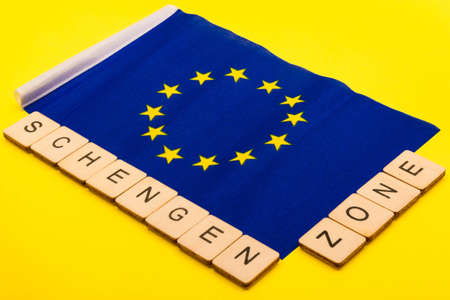European union concept showing the flag of the EU on a yellow background with a sign reading Schengen Zone Reklamní fotografie - 134424531