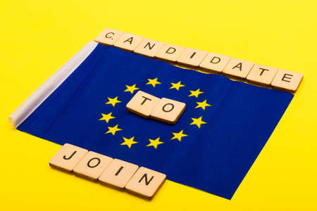 European union concept showing the flag of the EU on a yellow background with a sign reading Candidate to Join