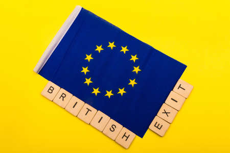 European union concept showing the flag of the EU on a yellow background with a sign reading British Exit