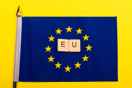 European union concept showing the flag of the EU on a yellow background with a sign reading EU