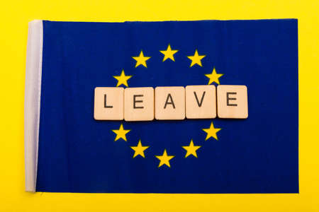 European union concept showing the flag of the EU on a yellow background with a sign reading Leave 写真素材