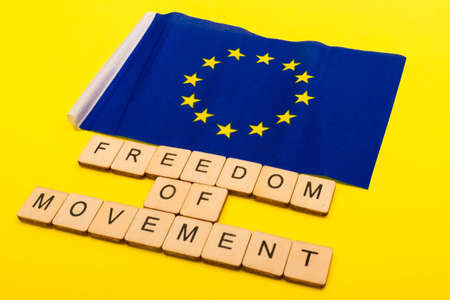 European union concept showing the flag of the EU on a yellow background with a sign reading Freedom of Movement