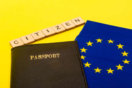 European union concept showing the flag of the EU and a passport on a yellow background with a sign reading Citizen