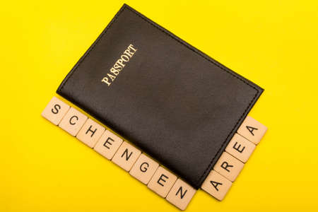 European union concept showing a passport a yellow background with a sign reading Schengen Area