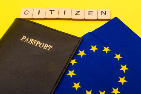 European union concept showing the flag of the EU and a passport on a yellow background with a sign reading Citizen Reklamní fotografie - 134424706