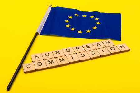European union concept showing the flag of the EU on a yellow background with a sign reading European Commission Reklamní fotografie - 134424710