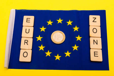 European union concept showing the flag of the EU on a yellow background with a sign reading Europ Zone and a one Euro Coin