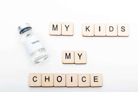 Vaccine concept showing a medical vial with a Vaccine label on a white background along with a sign reading My Kids My Choice