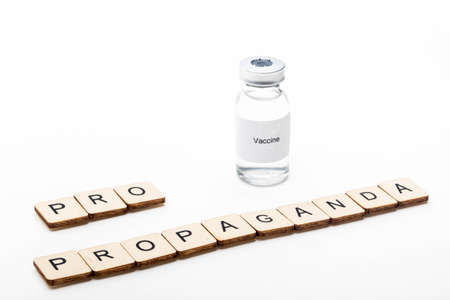 Vaccine concept showing a medical vial with a Vaccine label on a white background along with a sign reading Pro Propaganda Reklamní fotografie