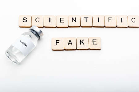Vaccine concept showing a medical vial with a Vaccine label on a white background along with a sign reading Scientific Fake