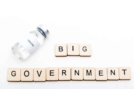 Vaccine concept showing a medical vial with a Vaccine label on a white background along with a sign reading Big Government