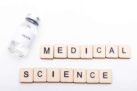Vaccine concept showing a medical vial with a Vaccine label on a white background along with a sign reading Medical Science Reklamní fotografie