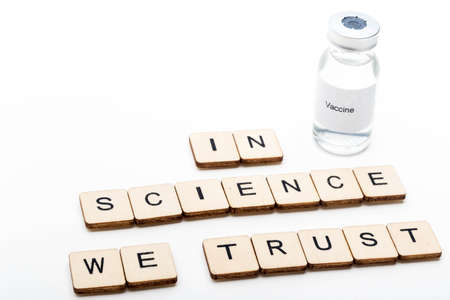 Vaccine concept showing a medical vial with a Vaccine label on a white background along with a sign reading In Science We Trust