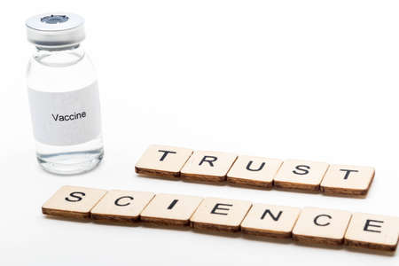Vaccine concept showing a medical vial with a Vaccine label on a white background along with a sign reading Trust Science Reklamní fotografie