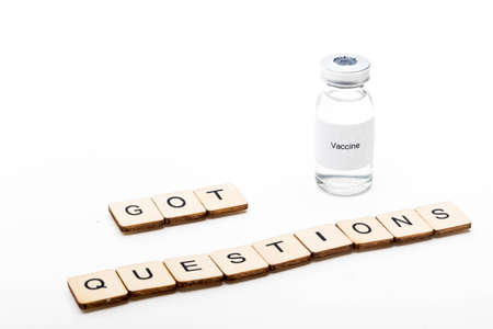 Vaccine concept showing a medical vial with a Vaccine label on a white background along with a sign reading Got Questions