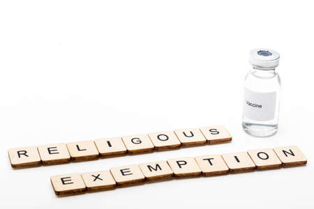 Vaccine concept showing a medical vial with a Vaccine label on a white background along with a sign reading Religous Exemption Reklamní fotografie