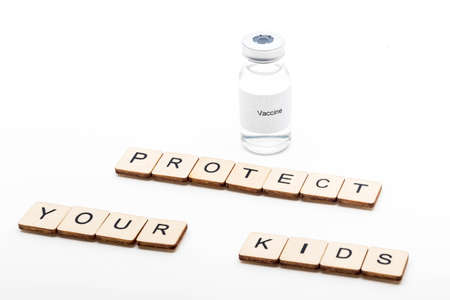 Vaccine concept showing a medical vial with a Vaccine label on a white background along with a sign reading Protect Your Kids