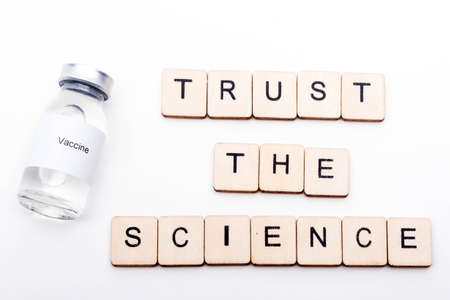 Vaccine concept showing a medical vial with a Vaccine label on a white background along with a sign reading Trust The Science Reklamní fotografie
