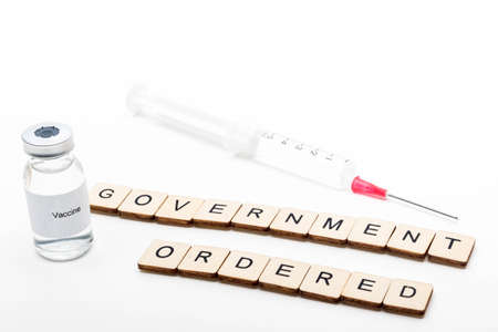 Vaccine concept showing a medical vial with a Vaccine label on a white background along with a sign reading Government Ordered with a syringe