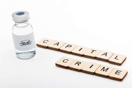 A glass medical vial with a skull and crossbones on a white background with a sign reading Capital Crime