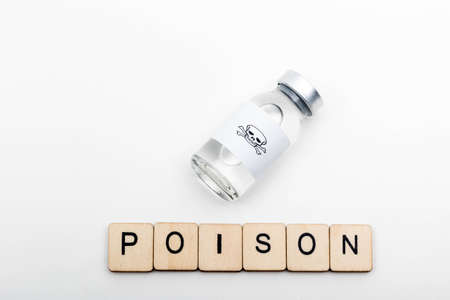 A glass medical vial with a skull and crossbones on a white background with a sign reading Poison 版權商用圖片