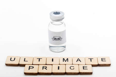 A glass medical vial with a skull and crossbones on a white background with a sign reading Ultimate price Stock Photo