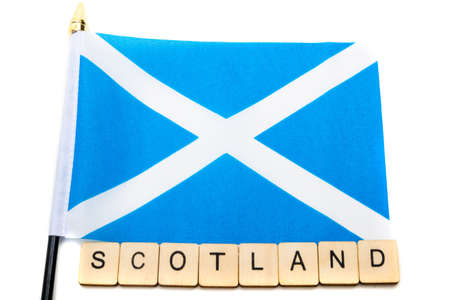 The national flag of Scotland, the Saltaire or cross of St Andrews on a white background with a sign reading Scotland