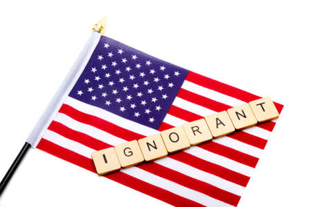 The flag of the United States isolated on a white background with a sign reading Ignorant