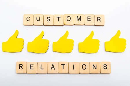 Customer feedback concept showing five yellow hands isolated on a plain background showing a sign reading customer relations and five thumbs up