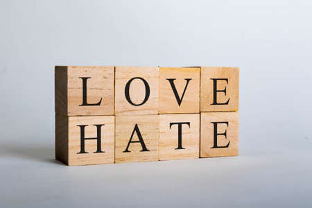 Wooden cubes with lettering spelling Love Hate. Concept that love beats hate Imagens