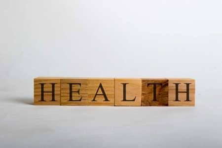 Wooden cubes with lettering spelling Health. Healthcare concept
