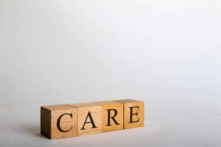 Wooden cubes with lettering spelling Care. Life or political concept Banco de Imagens