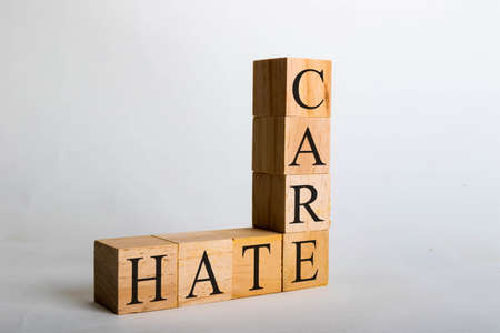 Wooden cubes with lettering spelling Care Hate. Concept that Care beats Hate