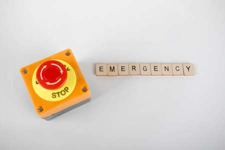 An industrial emergency stop button with a sign reading Emergency