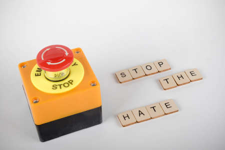 An industrial emergency stop button with a sign reading Stop The Hate