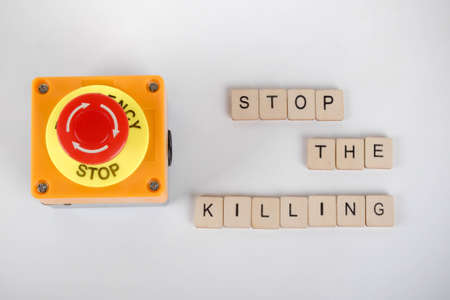 An industrial emergency stop button with a sign reading Stop The Killing