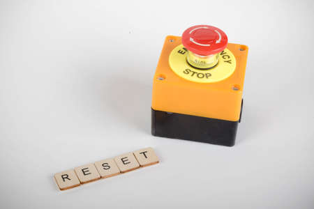 An industrial emergency stop button with a sign reading Reset