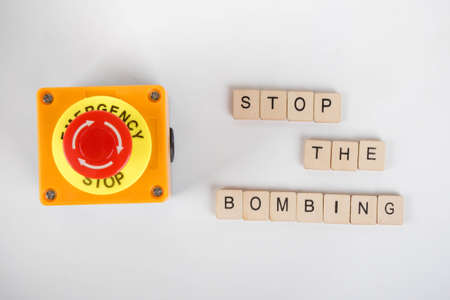 An industrial emergency stop button with a sign reading Stop The Bombing