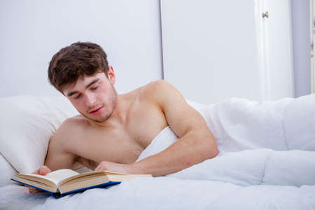 A young adult man, bare chested in bed reading a book Archivio Fotografico