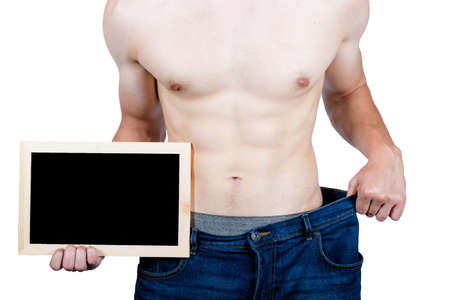 Weight losee concept showing a muscular young male adult holding put baggy clothing and holding a blackboard for slogans Archivio Fotografico