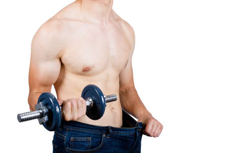 Weight losee concept showing a muscular young male adult holding put baggy clothing and holding a dumbbell Archivio Fotografico